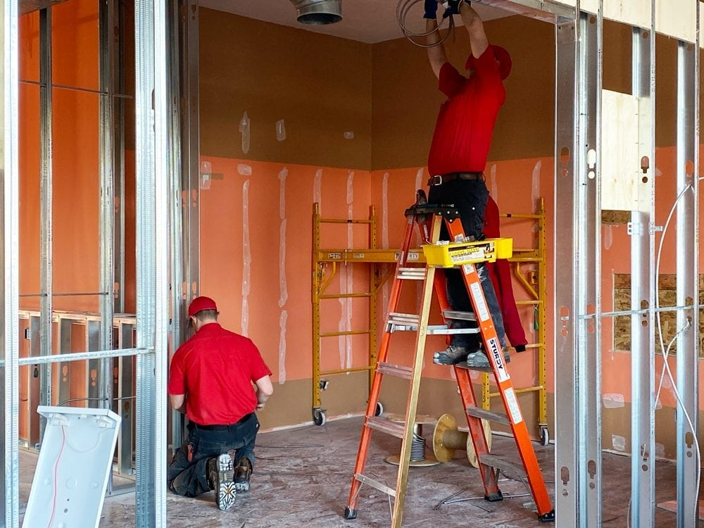 image of Exquisite Electric Electrican Dustin and electrical apprentice working on Okotoks business renovation